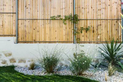 clôture habillée de lames en bois en guise de brise vue