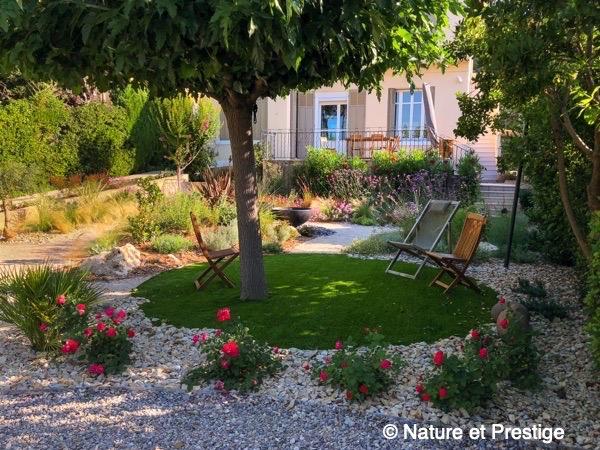 jardin plutôt aride avec plantes vivaces et pelouse synthétique sous ce magnifique mûrier platane